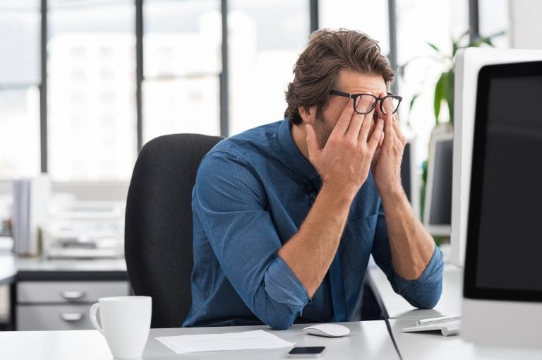 Portrait of an upset businessman at desk in office. Businessman