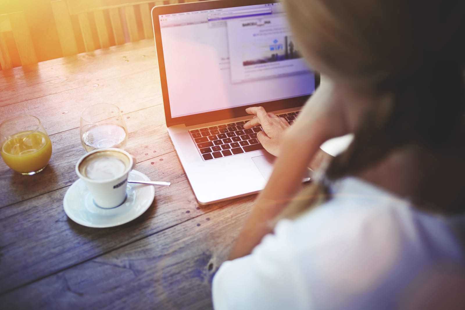 Young female person working on net-book while sitting in coffee shop