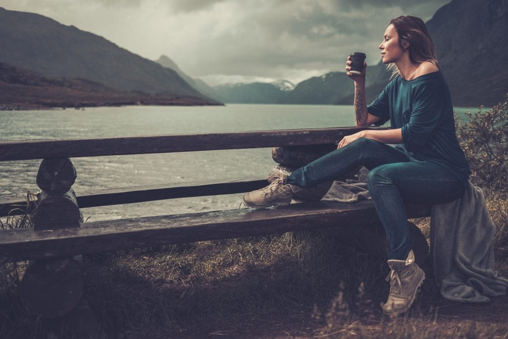 Confident woman with cup of coffee sitting near a body of water