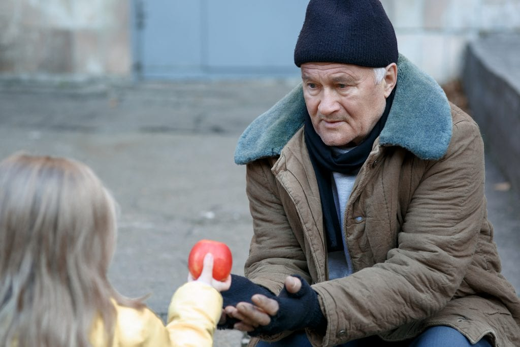 Young girl handing an apple to an old begger