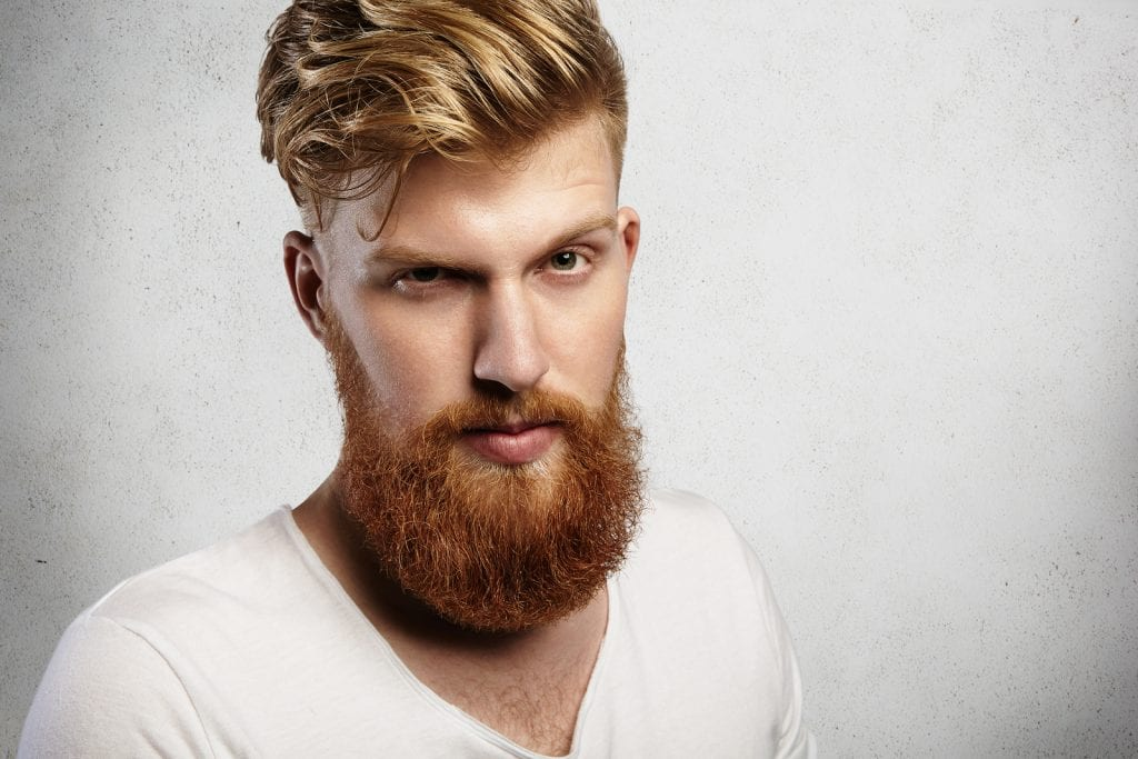 Portrait Of Young Handsome Hipster With Thick Red Beard