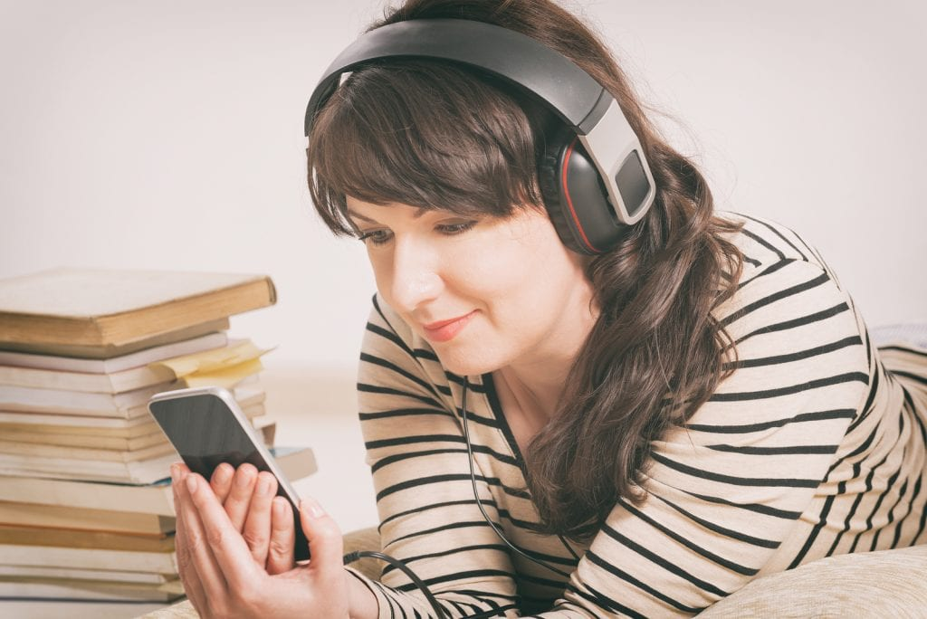Woman listening to audio books on her phone