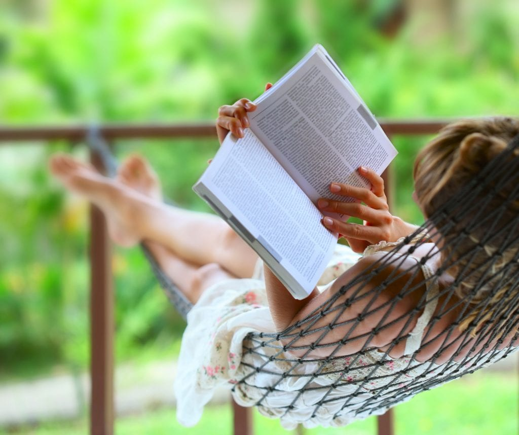 Young woman reading a book while lying in a hammock